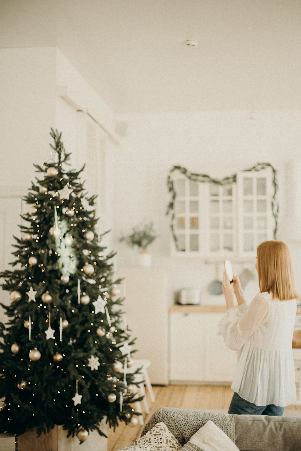 Woman taking photo of Christmas tree, Christmas captions for Instagram